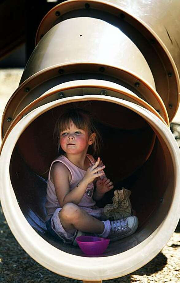 Mariah Schendel, 3, finds some shade inside a slide and eats her lunch at Todos Santos Plaza in Concord on Friday. Photo: Lance Iversen, The Chronicle