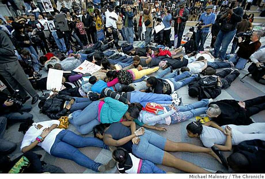 "Protesters drop to their stomachs in an arrest position, chanting ""Please don't shoot"" outside Oakland's city hall in a rally to protest the killing of Oscar Grant, killed by a BART police officer. Later, the protesters walked down 14th Street to to the Superior Court Building on Oak Street. Photo: Michael Maloney, The Chronicle"