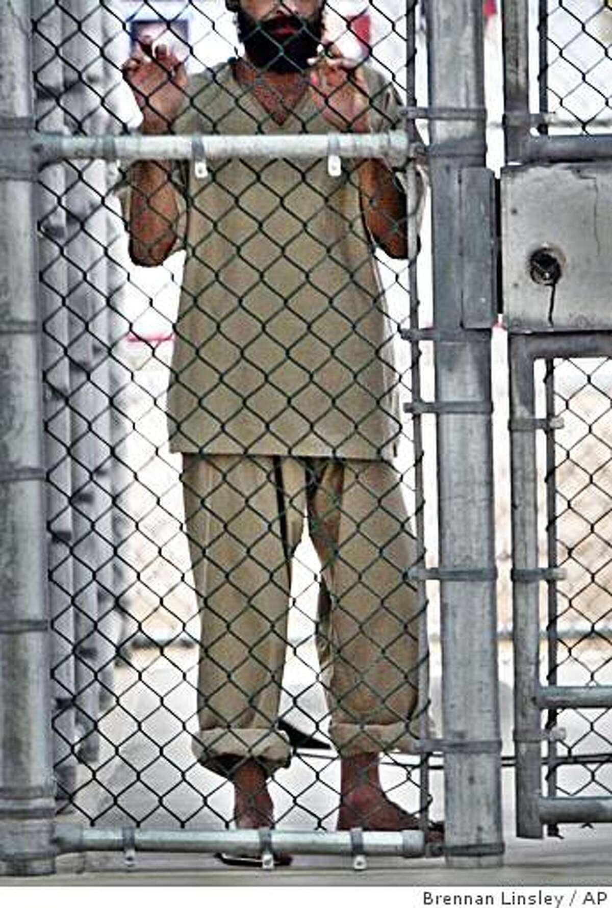 ** FILE ** In this June 26, 2006 file photo reviewed by the U.S. Military, a Guantanamo detainee holds onto a fence on the grounds of the maximum security prison at Camp 5, at Guantanamo Bay U.S. Naval Base, Cuba. A jury of six military officers reached a split verdict on Wednesday, Aug. 6, 2008, at Guantanamo Bay in the war crimes trial of Salim Ahmed Hamdan, a former driver for Osama bin Laden, clearing him of some charges but convicting him of others that could send him to prison for life. The judge scheduled a sentencing hearing for later Wednesday.(AP Photo/Brennan Linsley)