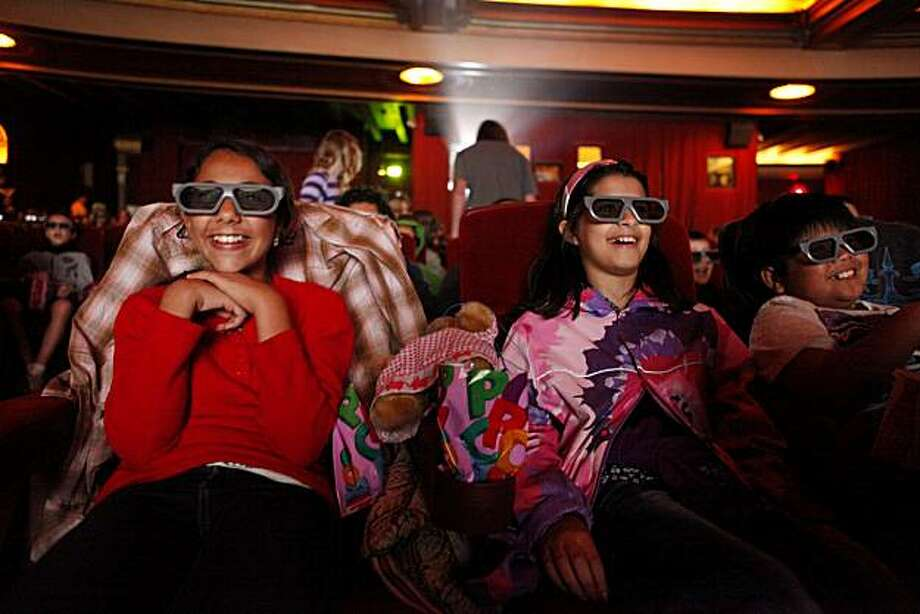 At the same time all of Oakland Unified teachers stage a  one day strike, fifth graders at Allendale Elementary School, Marla Wat, 10, Angelica Cueta, 10, and Erin Villanueva, 10,  join other school age kids from around the city for a 3D movie at the Grand Theater where the owner Allen Michaan offered a $5 matinee and popcorn special for displaced students on Thursday April 29, 2010. Photo: Mike Kepka, The Chronicle