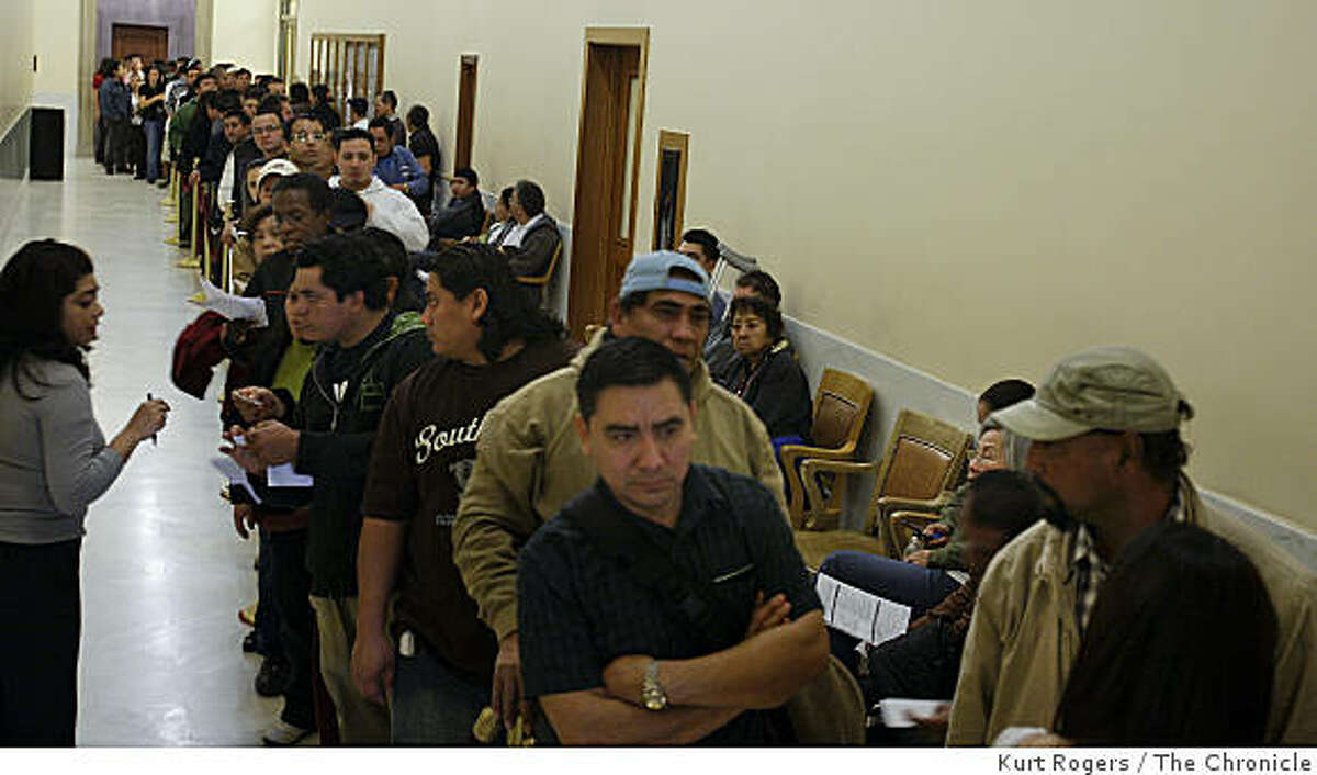 (Left) Maggie Zevallous with the Clerks office talks to people who are lined up inside the City Hall to get an appointment for new ID cards on Thursday Jan 15, 2009 in San Francisco , Calif.