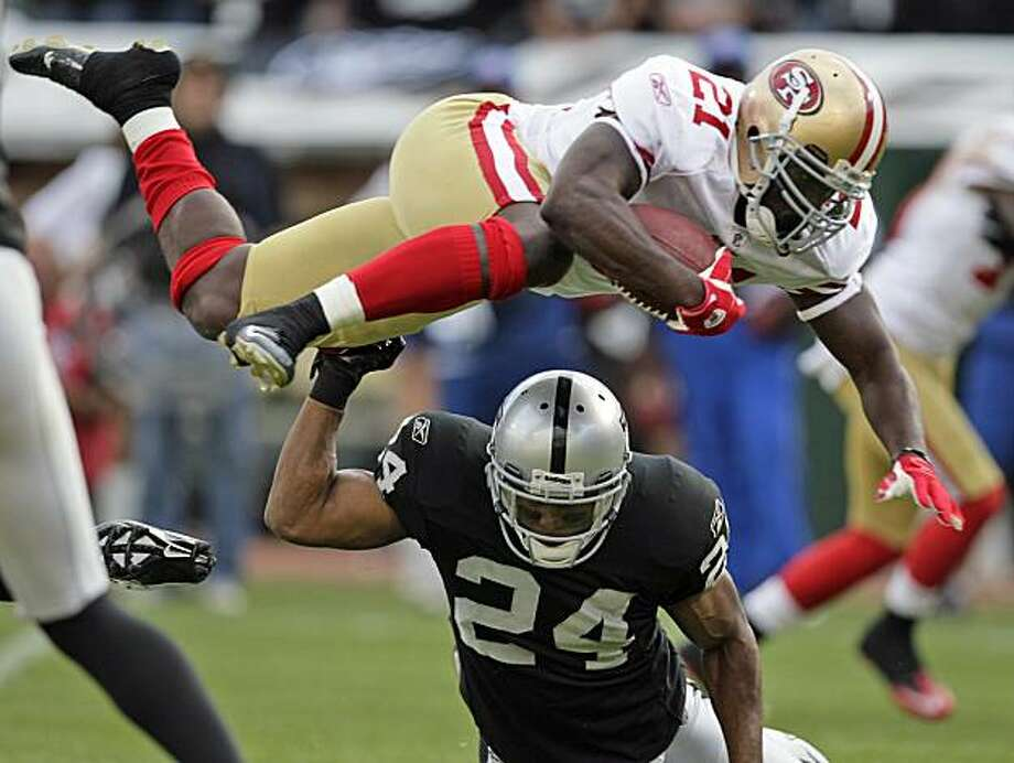 San Francisco 49ers running back Frank Gore, top, leaps over Oakland Raiders safety Michael Huff during the first half of a preseason NFL football game in Oakland, Calif., Saturday, Aug. 28, 2010. Photo: Ben Margot, AP