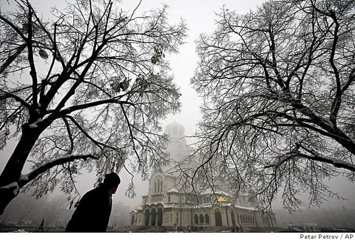 A man walks past the golden domed Alexander Nevski cathedral shrouded in winter mists in the Bulgarian capital Sofia, Monday, Jan. 12, 2009. A man is seen through an ice-covered window of a tram, in the Bulgarian capital Sofia, Monday, Jan. 12, 2009. Natural gas supplies from Russia through Ukraine to Bulgaria and other parts of Europe remain cut off for a seventh day, leaving several countries scrambling to secure alternative energy sources to cope with a cold winter, with factories shut down, schools closed and many thousands of people struggling to keep warm. (AP Photo/Petar Petrov)