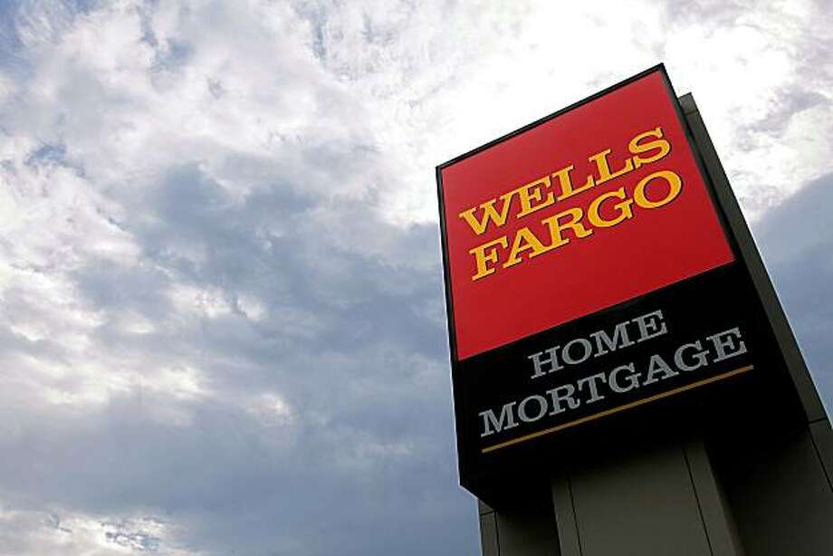 In this photograph taken July 19, 2010, the Wells Fargo logo is displayed on a sign outside one of the company's office buildings in Springfield, Ill. Wells Fargo & Co. said Wednesday, July 21, its second-quarter profit rose 21 percent as the growth of souring loans eased and it wrote off fewer defaults. Photo: Seth Perlman, AP