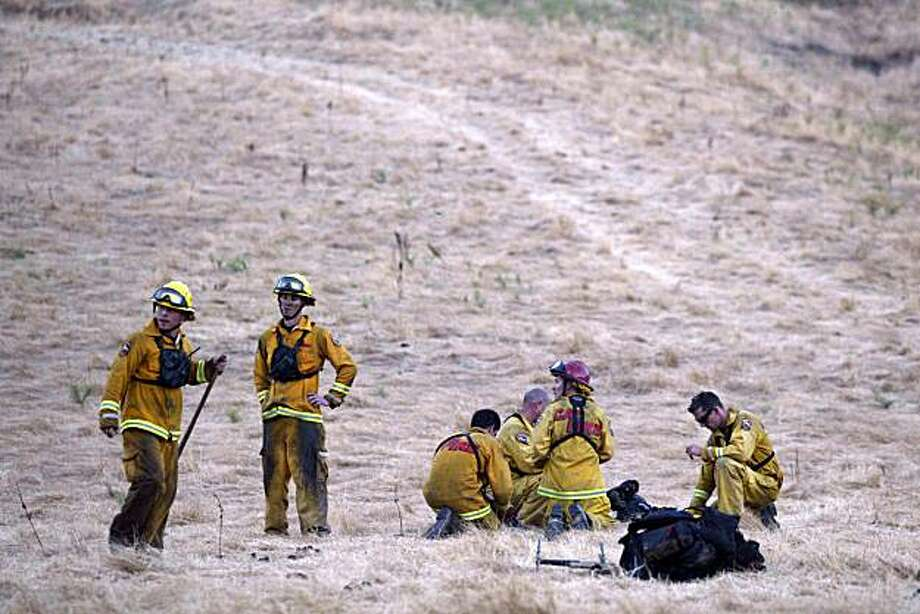 Cal Fire firefighters wait for a helicopter to pick them up up on the outskirts of Mount Diablo State Park in Clayton, Calif., on Tuesday, Aug. 24, 2010.  (Ray Chavez/Staff) ** MAGS OUT/MANDATORY CREDIT ** Photo: Ray Chavez, AP