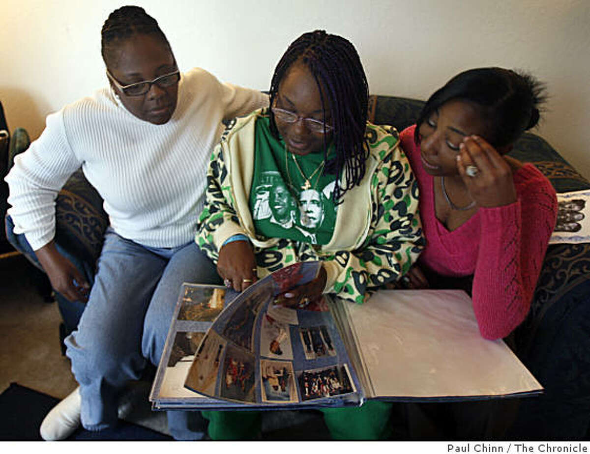 Carol Frazier, looks at family photos with her daughters Taneya Talley, center, and Shameana Talley at their home in Vallejo, Calif., on Wednesday, Nov. 26, 2008. Frazier's other daughter Taneka Talley was fatally stabbed to death in 2006 but Talley's insurance company is refusing to pay benefits to her son claiming the murder was racially motivated.