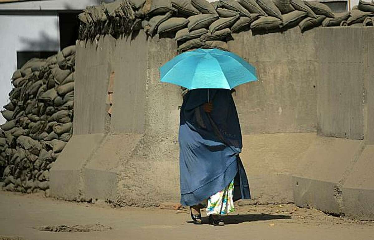 TOPSHOTS A burqa-clad Afghan woman uses an umbrella as she walks along a reinforced barrier in Kabul on August 23, 2010. Two NATO soldiers, one of them from the US, were killed in attacks in volatile regions of Afghanistan, the alliance said, a day afterfour US troops died in violence.