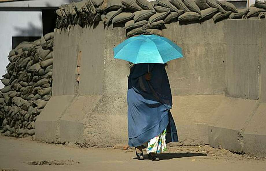 TOPSHOTS A burqa-clad Afghan woman uses an umbrella as she walks along a reinforced barrier in Kabul on August 23, 2010. Two NATO soldiers, one of them from the US, were killed in attacks in volatile regions of Afghanistan, the alliance said, a day afterfour US troops died in violence. Photo: Yuri Cortez, AFP/Getty Images