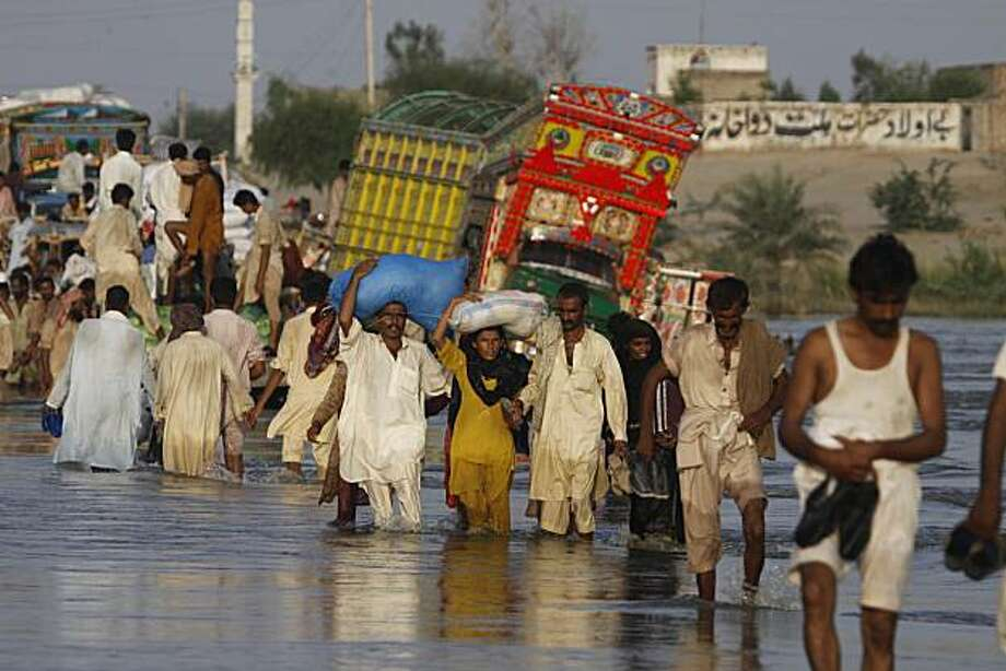Pakistanis cross a flooded road in Baseera, Punjab province, Pakistan on Monday Aug. 23, 2010. Workers piled stones and sandbags to plug leaks in a levee protecting a pair of southern Pakistani cities, as the floods that have destroyed homes, farmland andlivelihoods moved slowly toward the sea. Photo: Aaron Favila, Associated Press