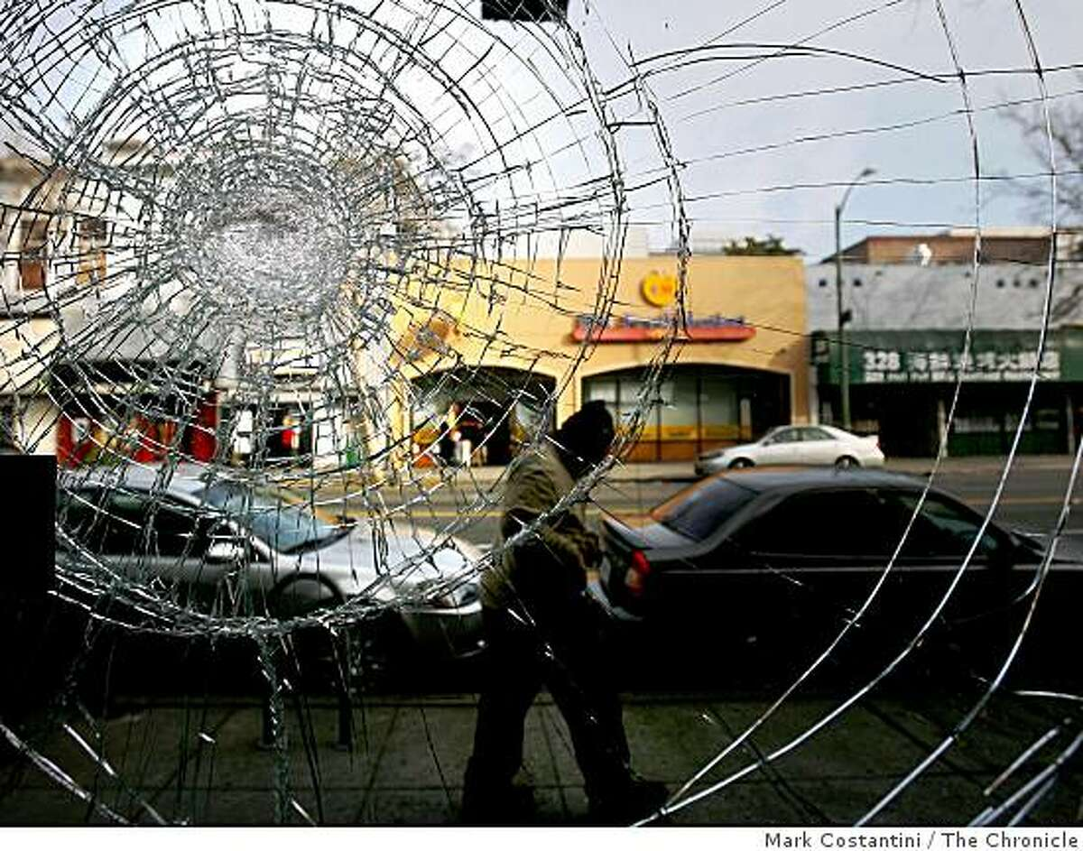 A man walks past the shattered glass door at Yoon's Pharmacy on 15th and Franklin Streets in Oakland Thursday morning.