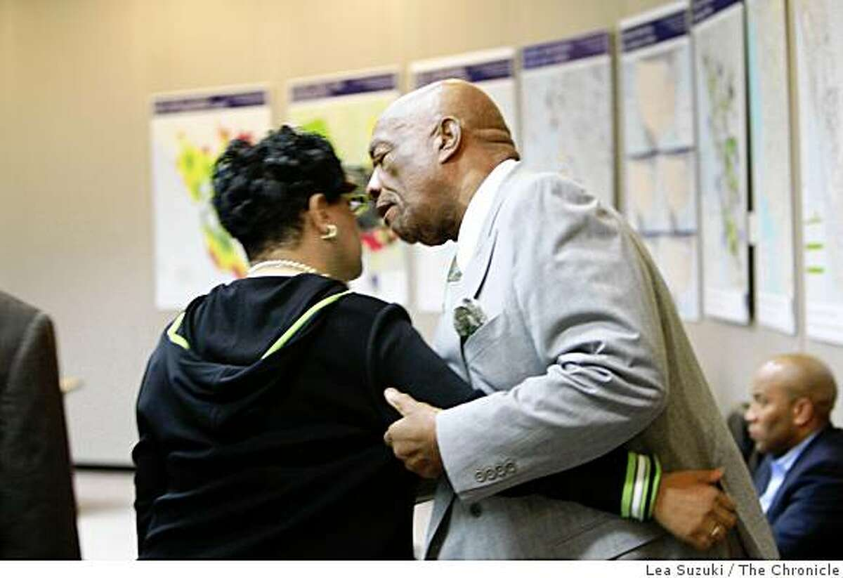 Charlie Walker of San Francisco (right) pulls Bart Board Member Carole Ward Allen (left) aside and talks with her as she reenters the Lawrence D. Dahms Auditorium after leaving during the community meeting in response to the shooting of Oscar Grant at the Joseph P. Bort MetroCenter in Oakland, Calif. on Sunday January 11 ,2009.