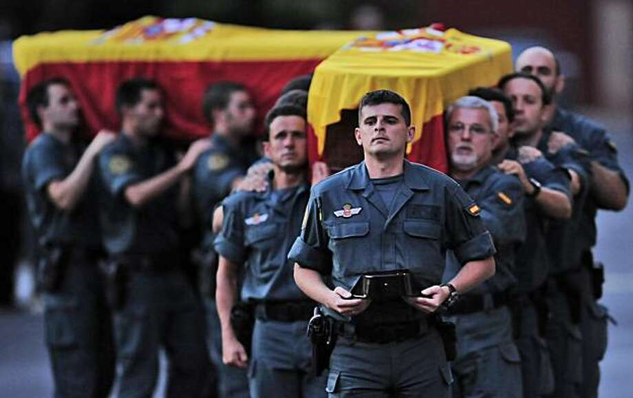 Brothers in arms carry the coffins of two Spanish Civil Guards killed in Afghanistan, during the funeral in central headquarters of Civil Guard in Logrono northern Spain, Thursday Aug. 26, 2010. Spanish Civil Guards,  Jose Maria Galera Cordoba, Leoncio Bravo Picallo and an Iranian-born interpreter Ataola Taefik Alili were killed by an Afghan man Wednesday at a NATO base during a training class for local police recruits. Photo: Alvaro Barrientos, AP