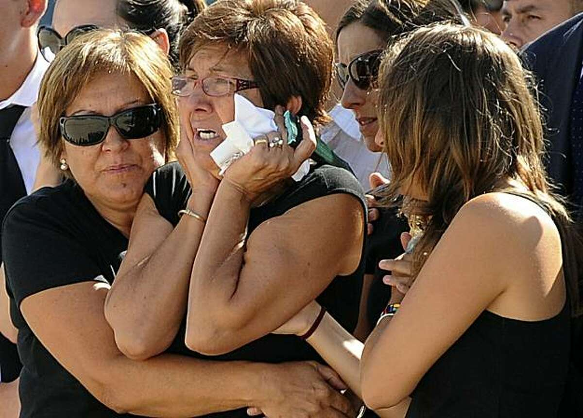 Relatives react upon the arrival of the bodies of two Spanish policemen and an interpreter killed in Afghanistan on August 26, 2010 in Madrid. The bodies of two Spanish policemen and an interpreter killed in Afghanistan arrived in Spain today where they were honoured in a ceremony attended by government officials. The coffins arrived in a Spanish air force plane at the military base of Torrejon outside Madrid. An Afghan employed as the driver of one of the two Civil Guard officers killed them and their Iranian-born Spanish interpreter during a training session in the northwestern province of Badghis on Tuesday before security forces shot him dead, Afghan and Spanish authorities said. TOPSHOTS /