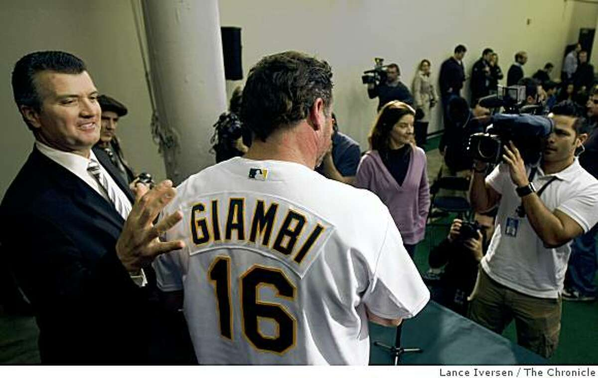 Oakland Athletics' manager Bob Geren pats his new free-agent designated hitter Jason Giambi, at a press conference in Oakland, Calif., Wednesday, Jan. 7, 2009.