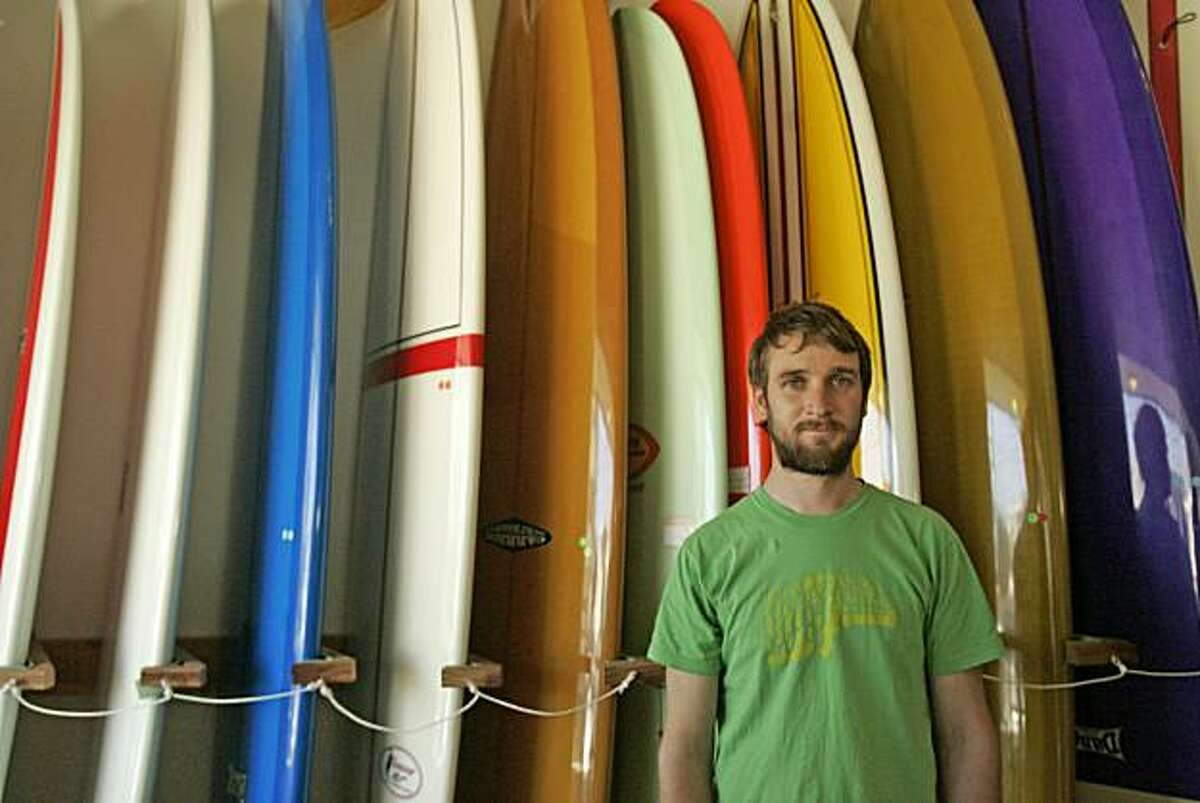 John McCambridge, of Mollusk Surf Shop, stands in front of a row of longboards in San Francisco, CA