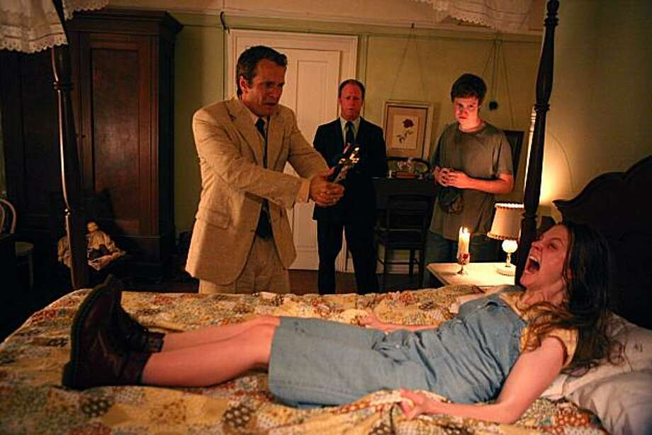 Nell Sweetzer (Ashley Bell, front), Cotton Marcus (Patrick Fabian, left), Louis Sweetzer (Louis Herthum, center), and Caleb Sweetzer (Caleb Landry Jones, right) in THE LAST EXORCISM. Photo: Patti Perret, Lionsgate