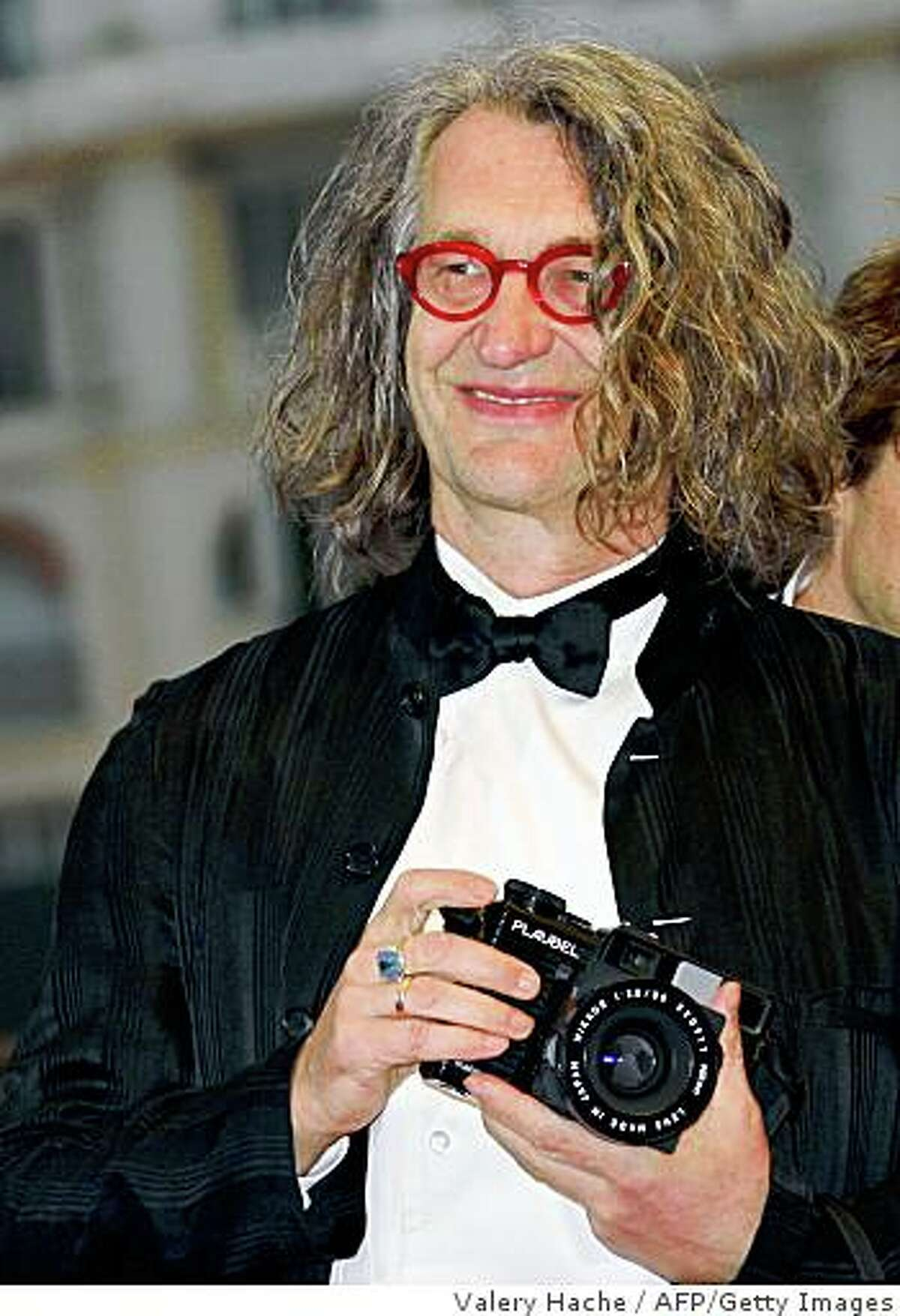 This picture taken on May 24, 2008, during the 61st International Cannes Film Festival shows German director Wim Wenders holding his camera as he poses upon arriving to attend the screening of his film 'The Palermo Shooting'. )