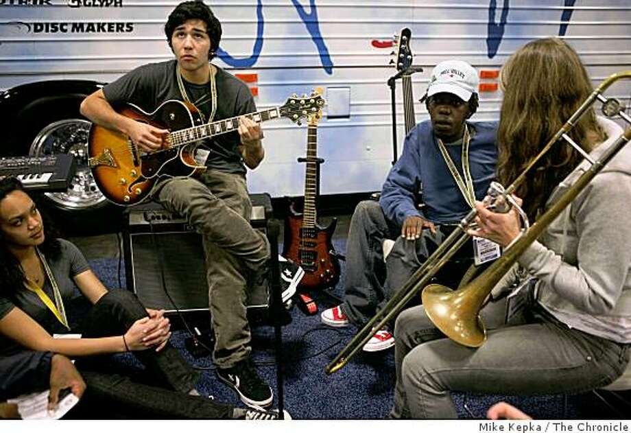 Surrounded by other young musicians from San Francisco and Zimbabwe, Adam Nash, a student from San Francisco's school of the Arts, works out a guitar part  with other young musicians in front of the John Lennon Educational Tour Bus at the Macworld conference and Expo on Monday Jan. 5, 2009 in San Francisco, Calif. Photo: Mike Kepka, The Chronicle