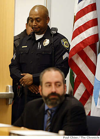 A BART police sergeant stands over BART director Tom Radulovich during a meeting attended by members of the public demanding answers about the shooting death of passenger Oscar Grant by a BART police officer. Photo: Paul Chinn, The Chronicle
