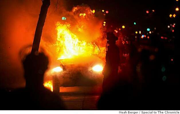 A car burns during rioting in downtown Oakland, Calif. on Wednesday, Jan. 7, 2009. Protesters, upset by the fatal shooting by a BART police officer of an unarmed man, smashed police cars, broke car windows and kicked in glass storefronts. Photo: Noah Berger, Special To The Chronicle