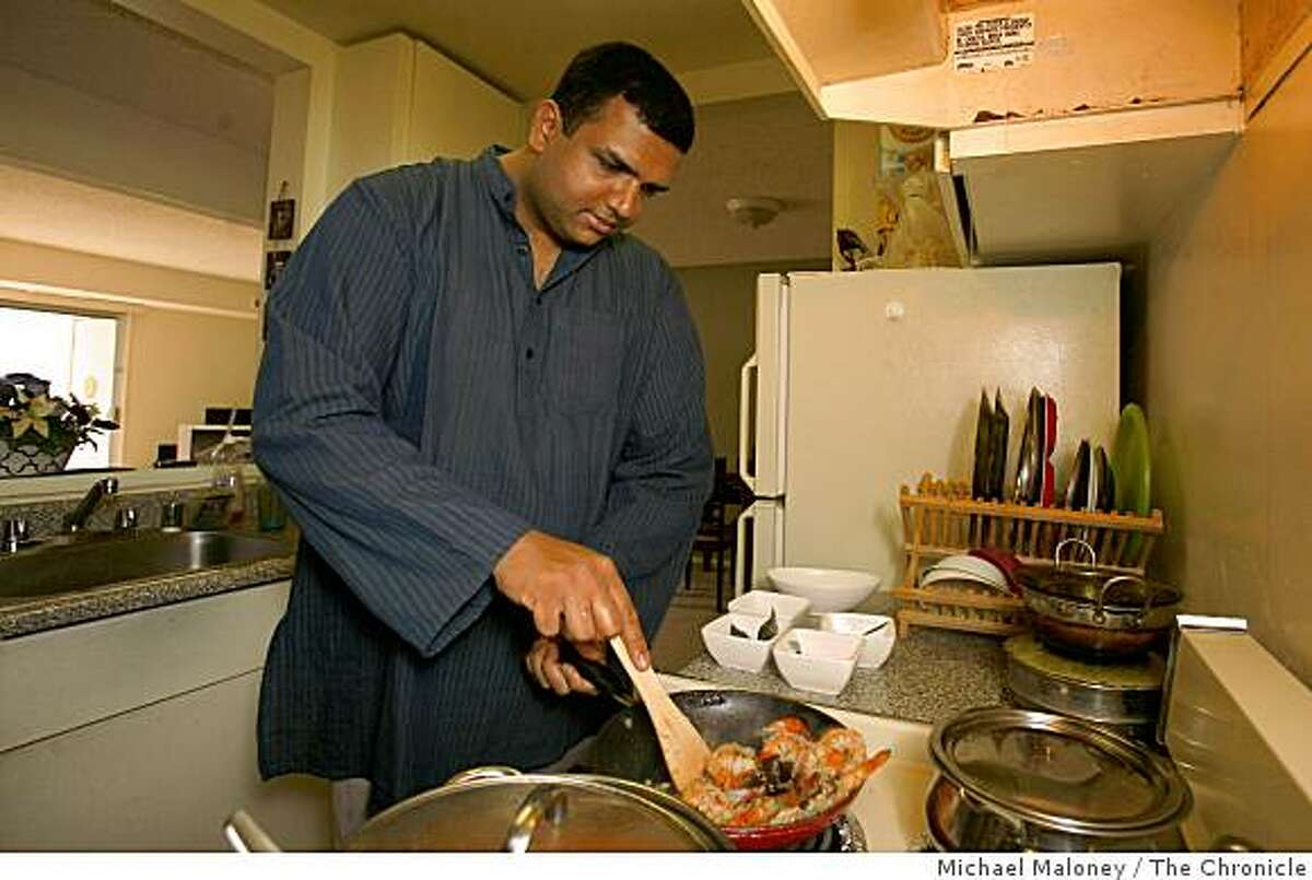 Amber India corporate chef Vittal Shetty prepares coconut shrimp curry in the small kitchen of his San Jose, Calif., apartment on December 3, 2008.