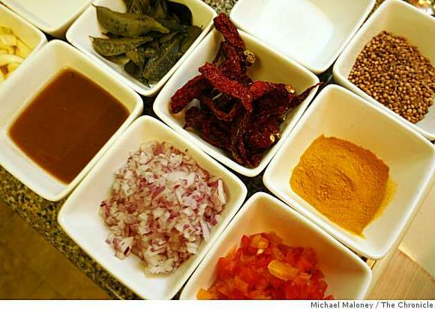 Some of the various spices and ingredients Amber India corporate chef Vittal Shetty uses for his coconut shrimp curry dish include garlic, coconut milk, red chilies, cilantro seeds, cumin seeds, tamarind juice, tomatoes, red onions, turmeric powder, mustard seeds, and curry leaves. Photo: Michael Maloney, The Chronicle