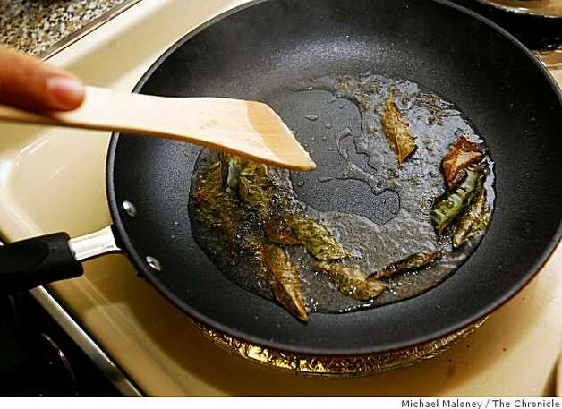 Amber India corporate chef Vittal Shetty heats curry leaves in hot oil, as he prepares coconut shrimp curry in the small kitchen of his San Jose apartment. Photo: Michael Maloney, The Chronicle