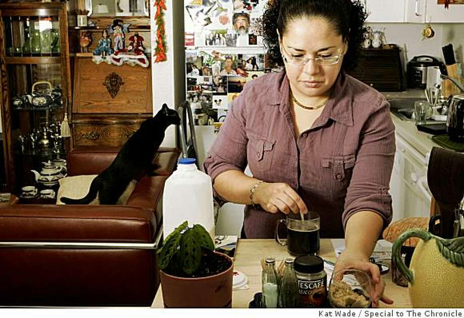 """Home owner, Lea Azucena, 30, says she is not """"petrified of the commitment of a mortgage because of two things. """"I have a lot of faith and I know that in a dynamic situation people come and go so it's up to me to take advantage of opportunities that arise as she opens her mortgage bill in San Francisco, Calif. on Tuesday, December 30, 2008. Photo: Kat Wade, Special To The Chronicle"""