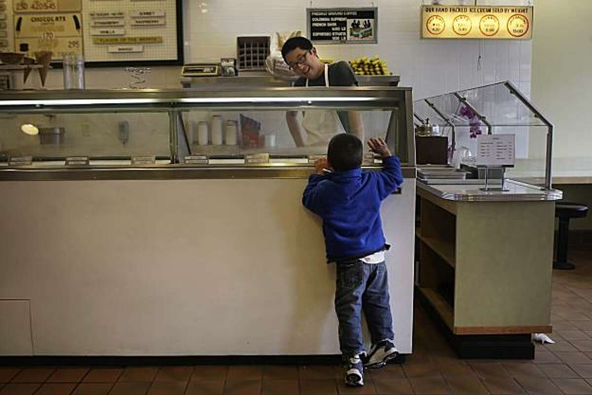Nash Garvens (l to r), 3, of San Francisco surveys the selection of ice cream while Satsuki Murashige greets him at Joe's Ice Cream in San Francisco, Calif. on Tuesday August 10, 2010.