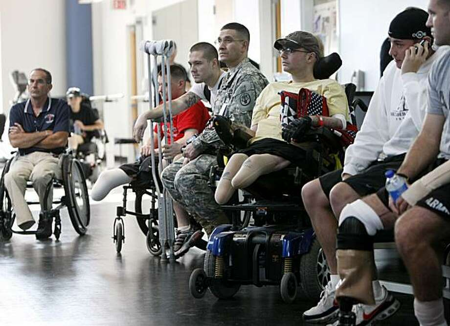 ** FILE ** In this Nov. 8, 2007 file photo, wounded soldiers involved in physical therapy wait for President Bush to visit a physical therapy lab for wounded soldiers at the Center For The Intrepid at the Brooke Army Medical Center in San Antonio. Lines of U.S. troops are limping away from the military with damaged bodies and minds, a surging increase in disabled veterans that will cost the nation billions for decades to come _ even as the total of America's vets from all wars has begun to shrink.  (AP Photo/Gerald Herbert, File) Photo: Gerald Herbert, AP