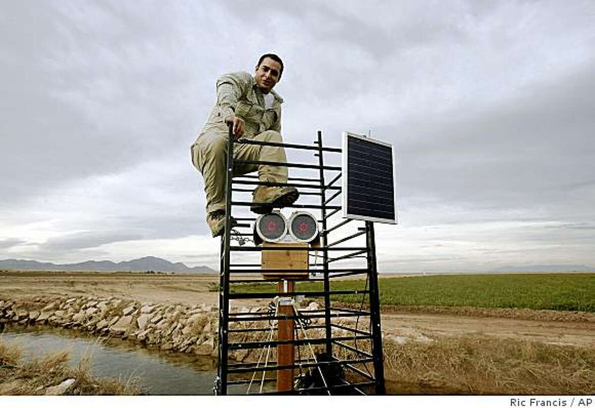 Samer Naif, a student at the University of California San Diego, sits atop a scinillometer transmitter in an Alfalfa field in Blythe, Calif. It's a laser device that measures evaporation and helps in calculating exactly how much water is needed to properly irrigate. (AP Photo/Ric Francis)