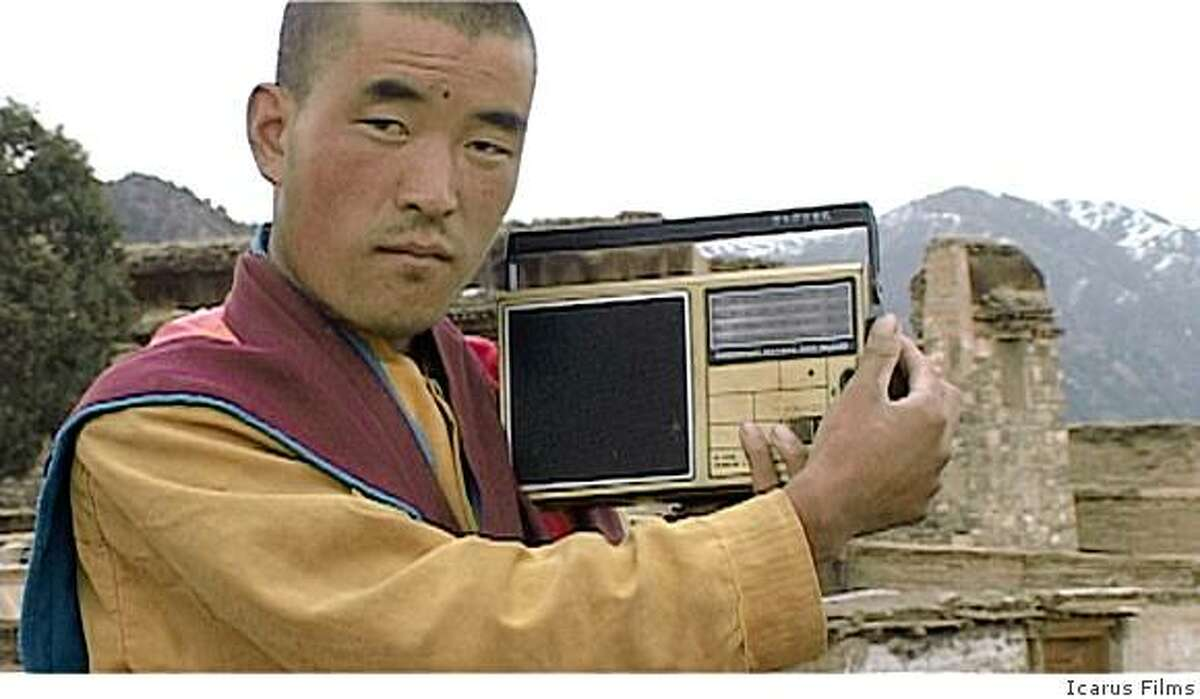 A Buddhist monk listens to news reports in ANGRY MONK: Reflections on Tibet, a feature documentary by Luc Schaedler.