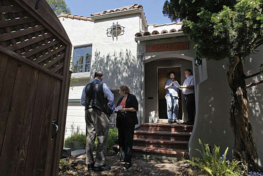 Glen Bell, (right) shows info to realtor, Norman Gee during a broker's tour in Berkeley, Calif. on Thursday August 19, 2010, where a bank-owned foreclosure property in the Berkeley Hills is going for an asking price of $899,000 Photo: Michael Macor, The Chronicle