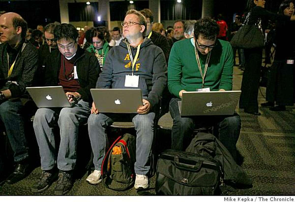 Macworld attendees Joe Leo (left), Peter Petersson and Joshua Topolsky await the latest Apple updates during Phil Schiller's keynote speech at Macworld.