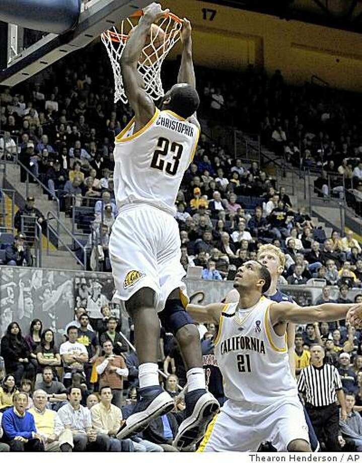 California Golden Bears' Patrick Christopher (23) stuffs the ball for two points as teammate Omondi Amoke (21) blocks out the Arizona Wildcats defense during second-half action of their NCAA college basketball game in Berkeley, Calif., Friday, Jan. 2, 2009. California won the game 69-55. (AP Photo/Thearon W. Henderson) Photo: Thearon Henderson, AP
