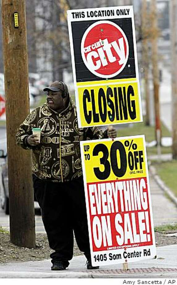 ** FILE ** In this Nov. 11, 2008 file photo, a worker holds an sign promoting the store-closing sale at the Circuit City store in Mayfield Heights, Ohio. Going-out-of-business sales for major retailers Linens 'N Things, Circuit City Stores Inc., Steve & Barry's LLC, KB Toys Inc. and others have flooded liquidators with goods to sell. Experts advise shoppers to approach these liquidation sales warily, since there's no guarantee they'll have the lowest prices. (AP Photo/Amy Sancetta, file) Photo: Amy Sancetta, AP