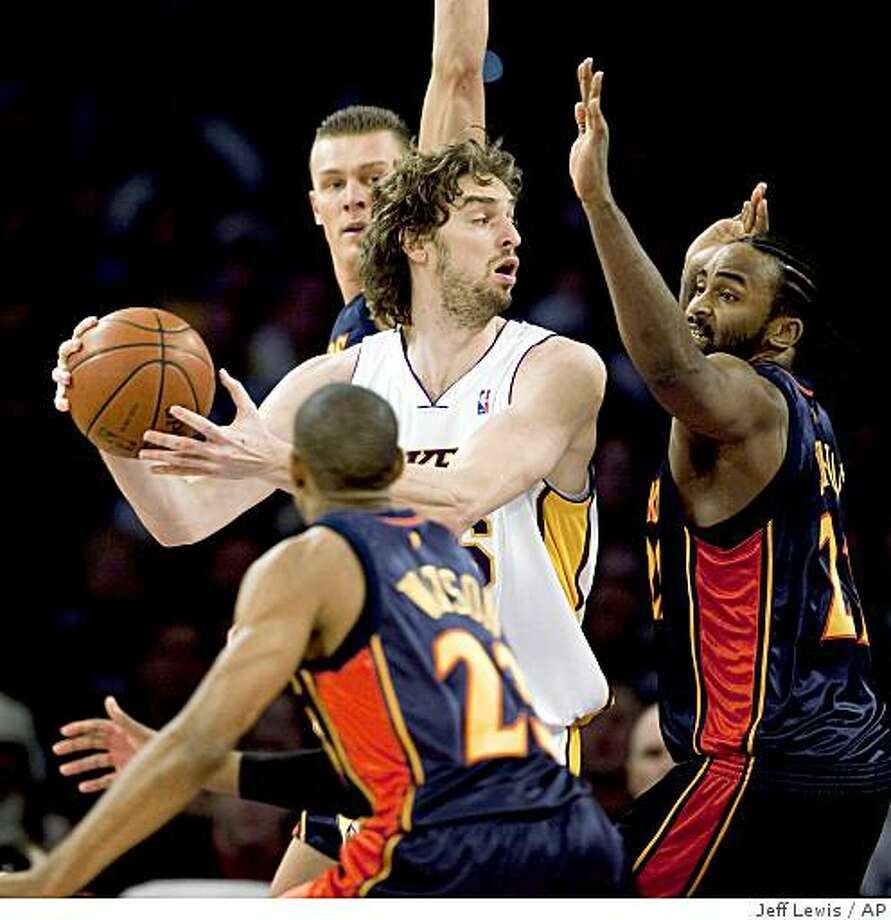 Los Angeles Lakers' Pau Gasol, of Spain, looks to pass while being guarded by Golden State Warriors' C.J. Watson, Andris Biedrins, rear, and Ronny Turiaf, right, during the first half in a game on Sunday, Dec. 28, 2008, in Los Angeles. Photo: Jeff Lewis, AP