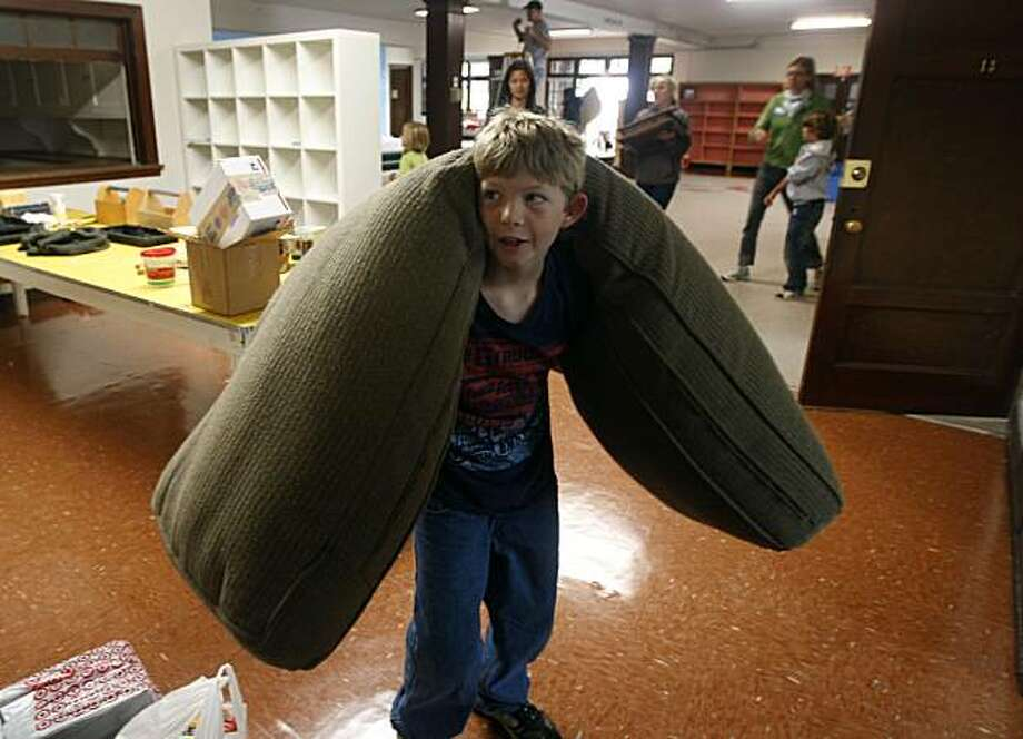Incoming student Miles Fries, 10, carries a cushion into the East Bay School for Boys to prepare for its inaugural year in Berkeley, Calif., on Saturday, Aug. 14, 2010. The school, which will use a curriculum designed specifically for boys, will open the Fall session with 18 sixth-grade students on Aug. 31. Photo: Paul Chinn, The Chronicle