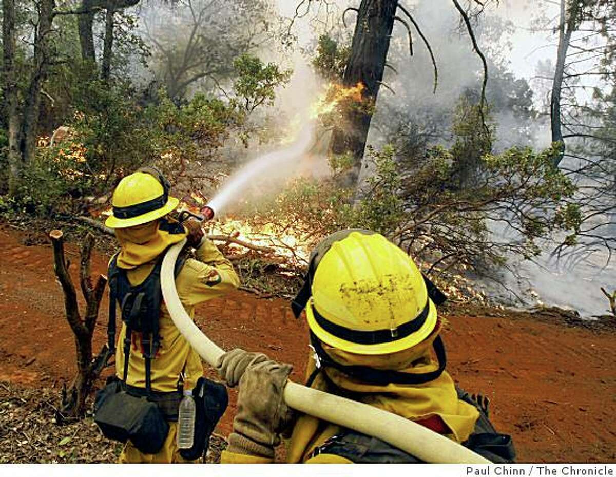 Firefighters Talon Sutherland, left, and Kody Dribnak hose down flames advancing towards a home in Concow, Calif., on July 9, 2008.