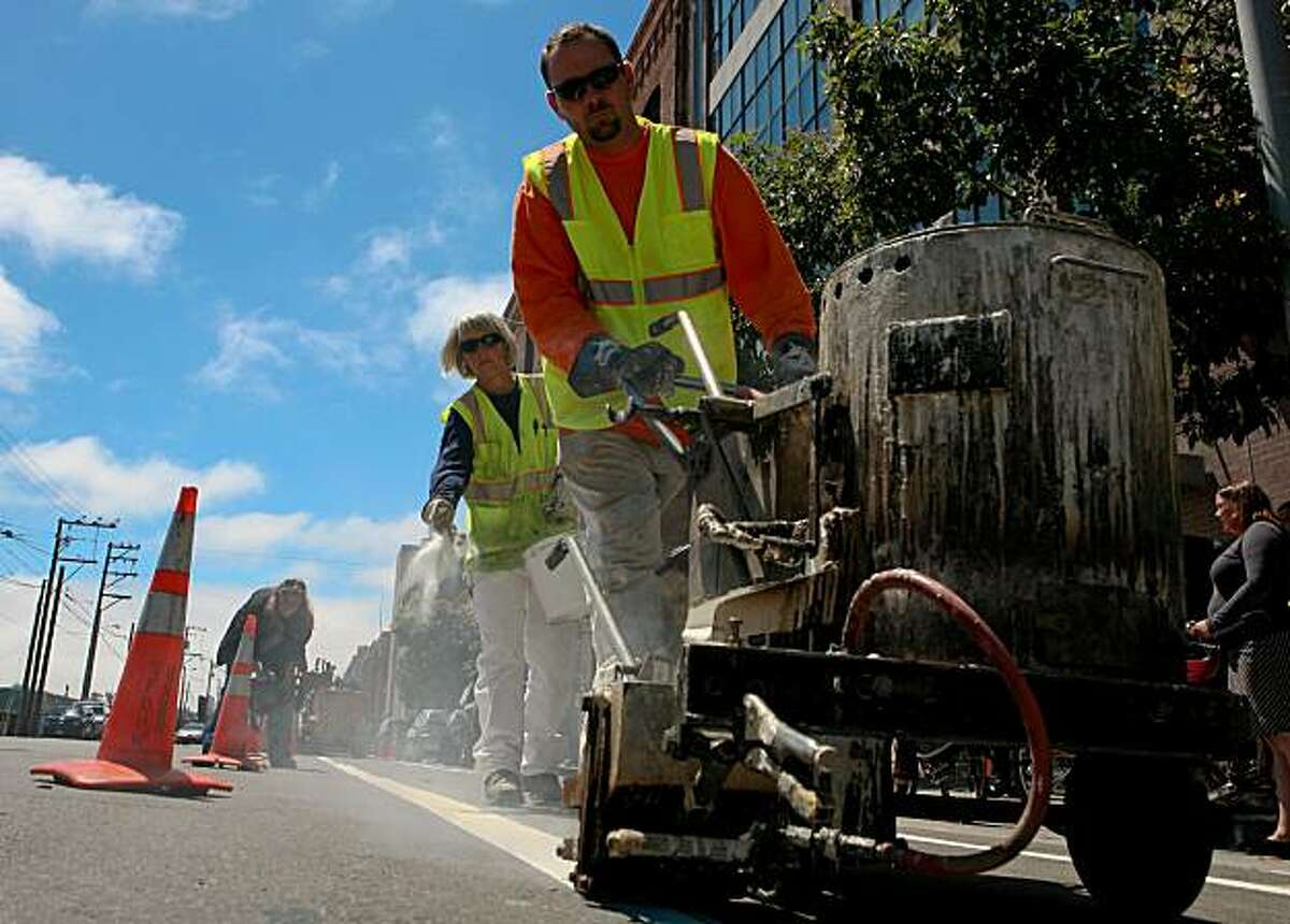 Municipal Transit Authority (MTA) worker David Rickard paints the second line as coworker Janie Hillyer spreads the reflective glass beads as they install the new bike lane on the corner of Fourth Street and Townsend on Monday, August 9, 2010 in San Francisco, Calif.
