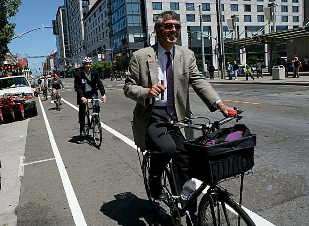Andy Thornley of the San Francisco Bicycle Coalition holds a cigar as he is one of many to ride down the newly painted bike lane on the corner of Fourth Street and Townsend on Monday, August 9, 2010 in San Francisco, Calif.