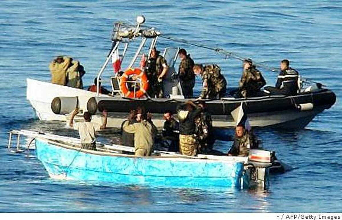 """BEST QUALITY AVAILABLE- This handout photo released by the French Ministry of Defense on January 1, 2009 shows French soldiers arresting presumed Somali pirates in the eastern part of the Golf of Aden off the Somali coast. Eight pirates where apprehended whilst trying to hijack the cargo vessel S. Venus. flying a Panamanian flag and have been placed aboard the French frigate """"Premier Ma�tre L'Her"""" before their handing over to Somalian authorities. AFP PHOTO MINISTERE DE LA DEFENSE (Photo credit should read -/AFP/Getty Images)"""