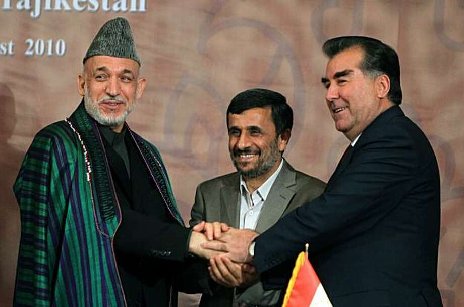 Afghanistan President Hamid Karzai (L) shakes hands with his counterparts from Iran's Mahmoud Ahmadinejad (C) and Tajikistan's Emomali Rakhmon (R) in Tehran on August 05, 2010 at the Trilateral Summit. Photo: Atta Kenare, AFP/Getty Images
