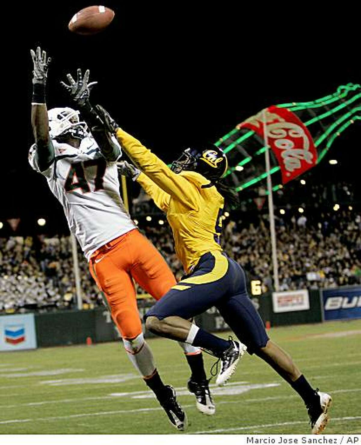 Miami wide receiver Laron Byrd (47) reaches for a pass in the end zone as California cornerback Syd'Quan Thompson defends in the second half of the Emerald Bowl NCAA college football game in San Francisco, Saturday, Dec. 27, 2008. Byrd dropped the ball. California won 24-17. (AP Photo/Marcio Jose Sanchez)