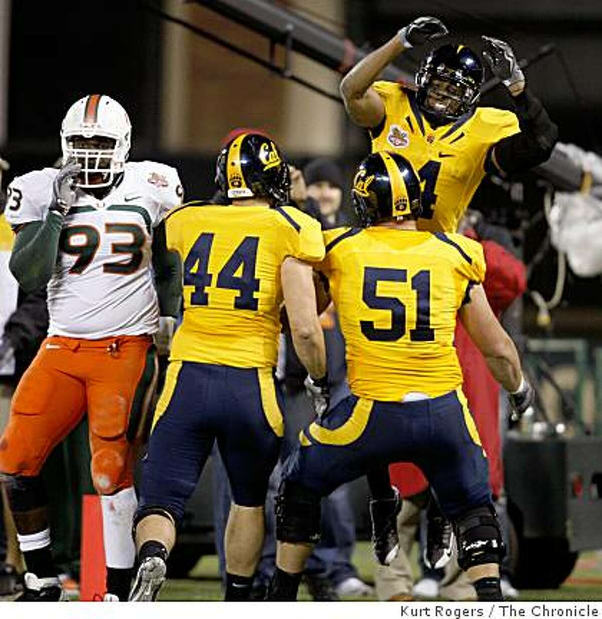 Cal's Jahvid Best (4) celebrates in the endzone with teammates Tad Smith (44) and Alex Mack (51) as Miami's Dwayne Hendricks (93) looks on after a first quarter touchdown in the Emerald Bowl at AT&T park in San Francisco, Calif., on Saturday, December 27, 2008.