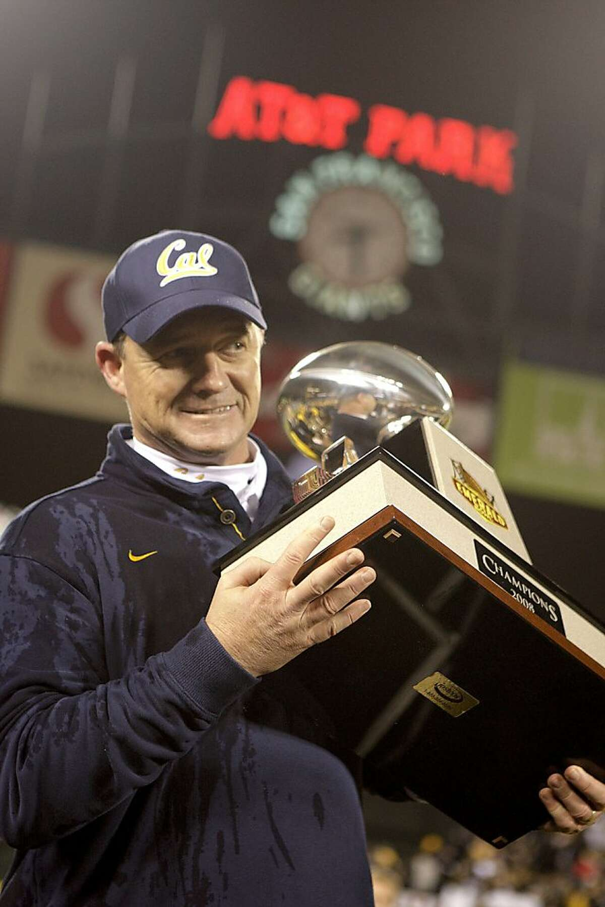 Jeff Tedford takes the Emerald Bowl trophy with him as he walks back to the locker room . on Saturday Dec 27, 2008 in San Francisco , Calif