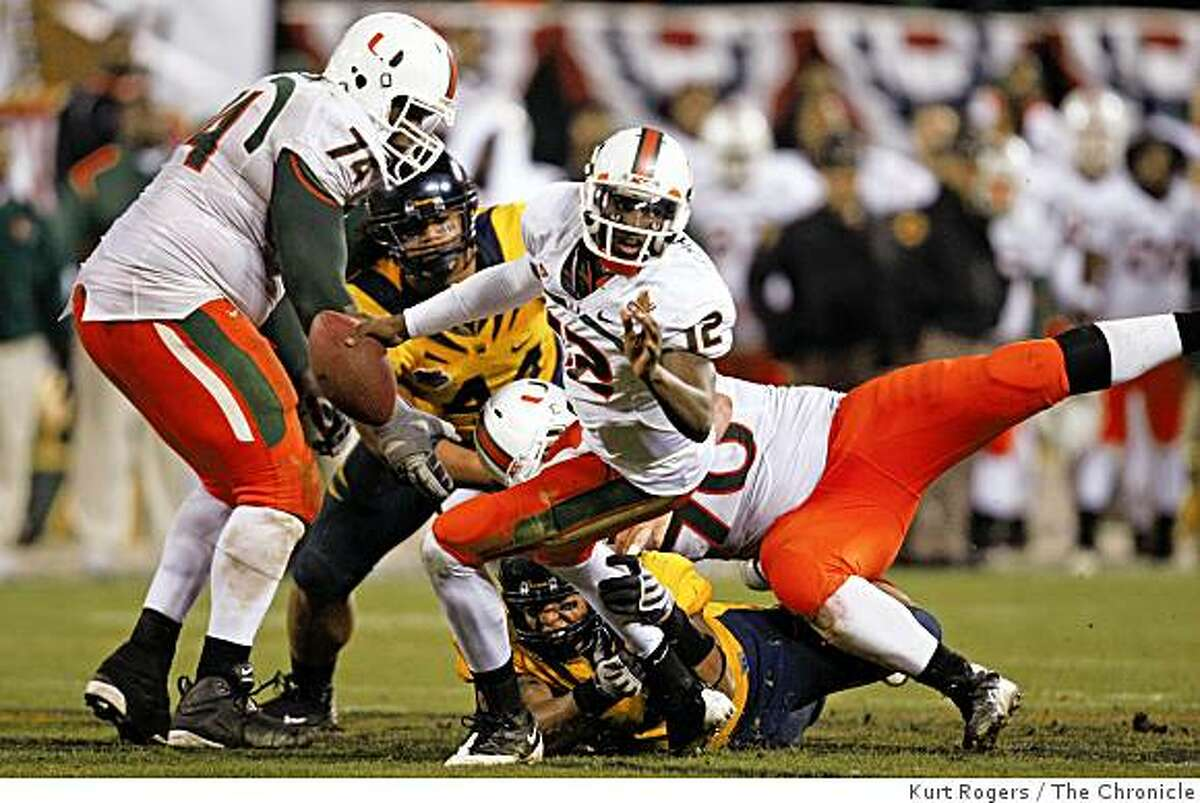 Miami's Jacory Harris scrambles away from Cal defenders on the last play of the game in the Emerald Bowl on Saturday, Dec 27, 2008 in San Francisco, Calif.