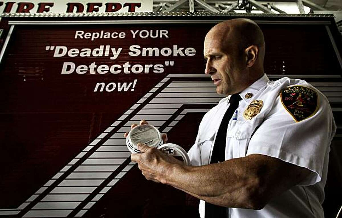 Albany Fire Chief Marc McGinn, holds a photoelectric smoke detector at the Albany FIre Station in Albany, Calif. on Tuesday August 10, 2010. McGinn is calling for the immediate removal of what he claims are fraudulent, ?'deadly?