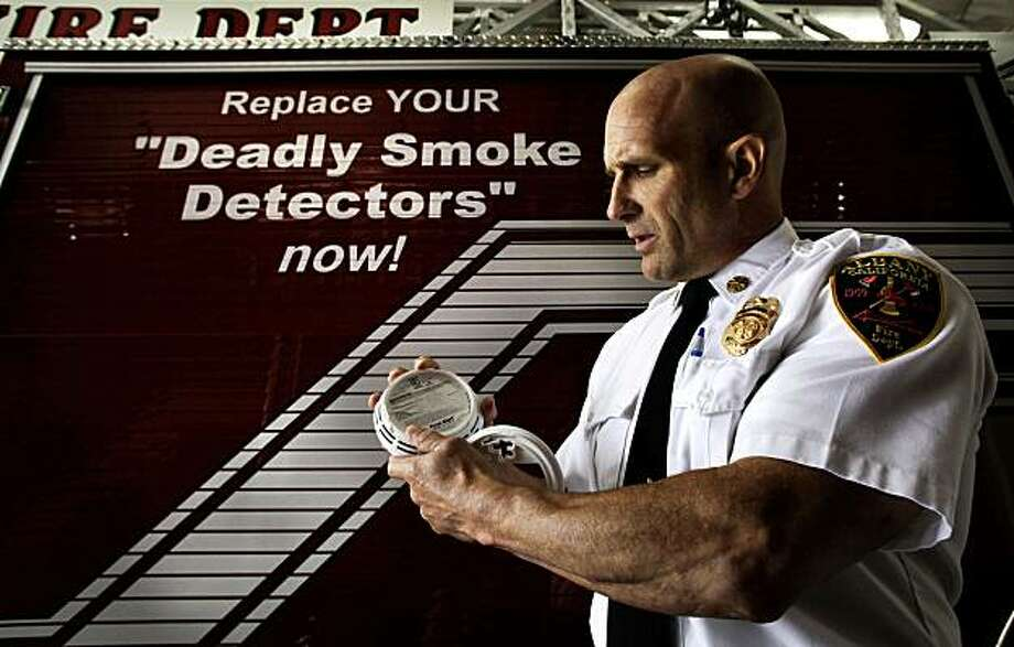 Albany Fire Chief Marc McGinn, holds a photoelectric smoke detector at the Albany FIre Station in Albany, Calif. on Tuesday August 10, 2010. McGinn is calling for the immediate removal of what he claims are fraudulent, ÒdeadlyÓ ionization so-called smoke alarms from all stores and homes in America and replacing them with photoelectric devices. Photo: Michael Macor, The Chronicle