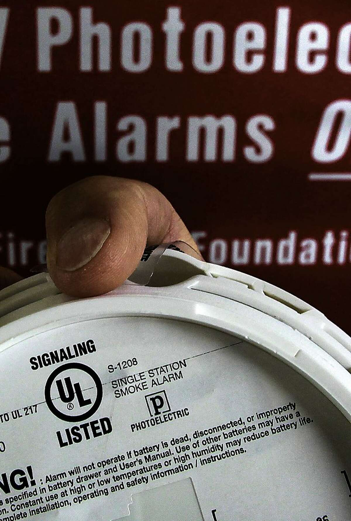Fire Chief Marc McGinn displays the back of a photoelectric smoke detector which displays a